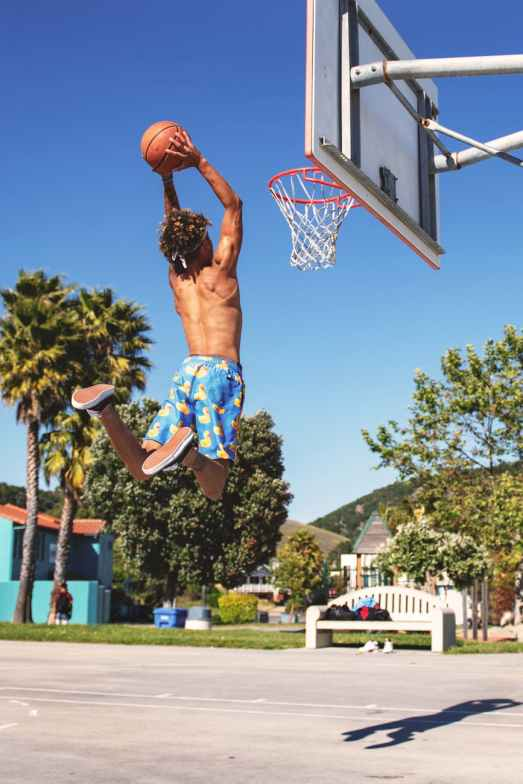man wearing blue and yellow shorts playing basketball