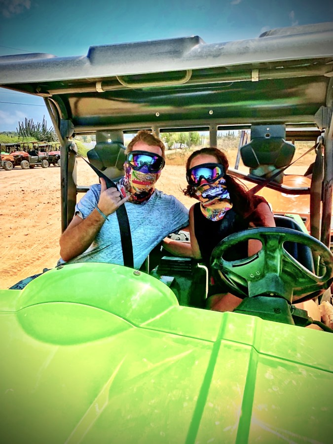 Couple sitting in UTV with eye and mouth guards to protect their faces from dust
