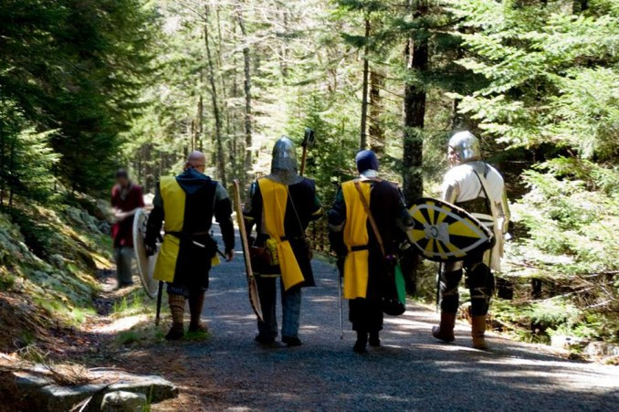Photo of the backs of four heavy list fighters wearing armor and black & yellow tabards walking ahead of the photographer along the beautiful Acadia National Park carriage road.