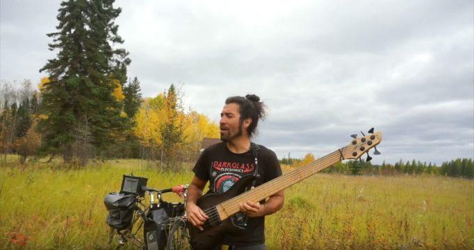 草原でベースを弾くフェリペ・ゴメスさん