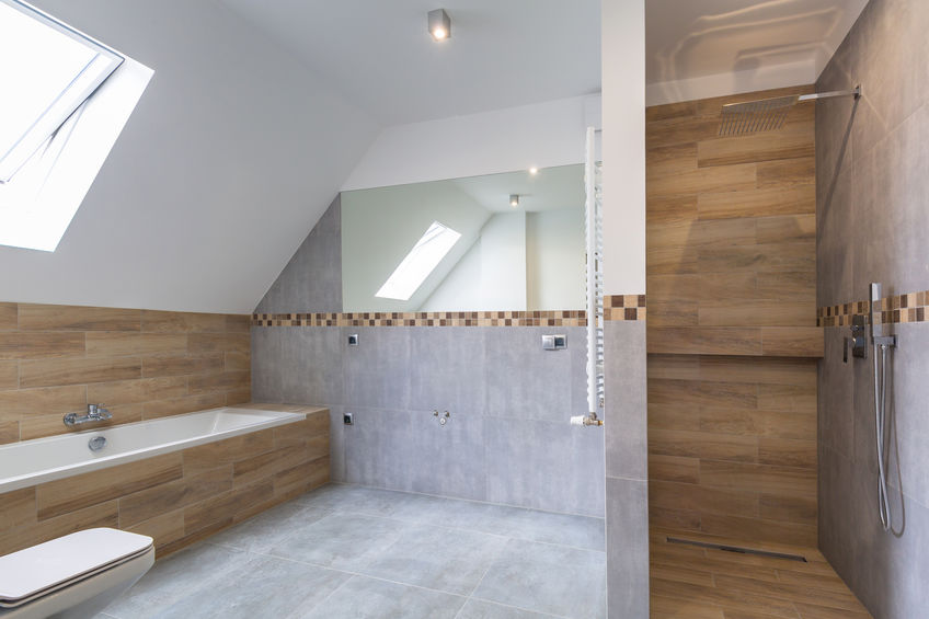 New bathroom interior in the house. Gray concrete tiles with wooden decor.