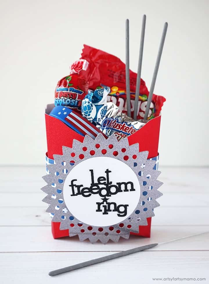 "A red gift box with a sparkly sign that says ""let freedom ring. """