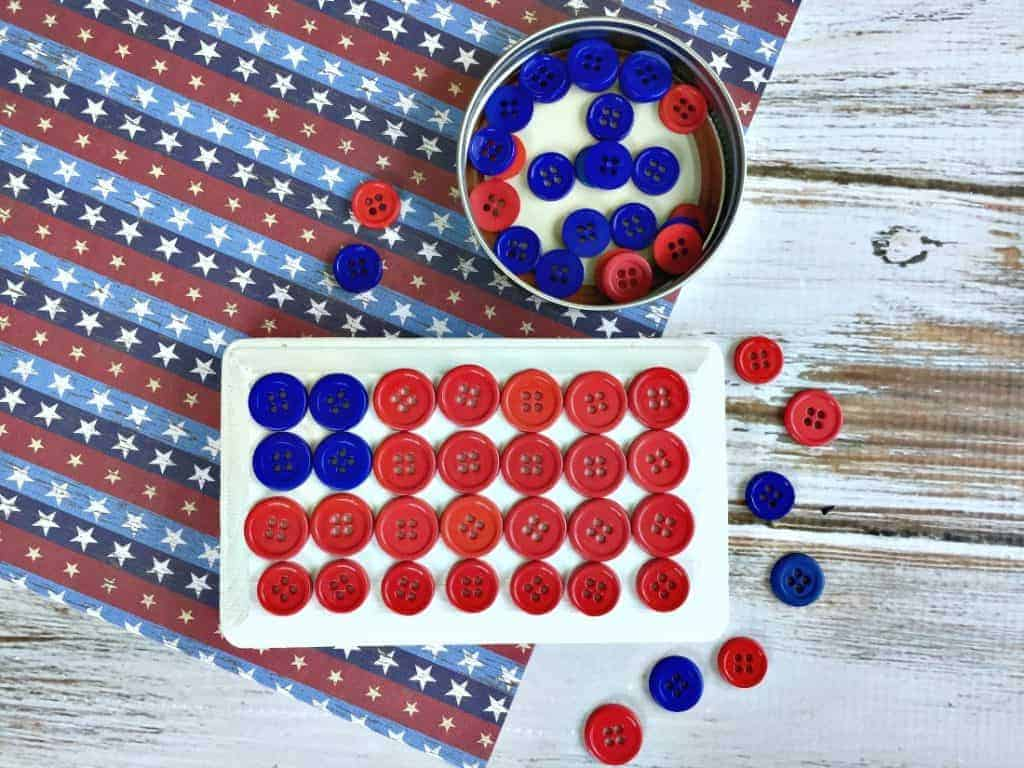 A white plaque with red and blue buttons glued to it to make an American flag.
