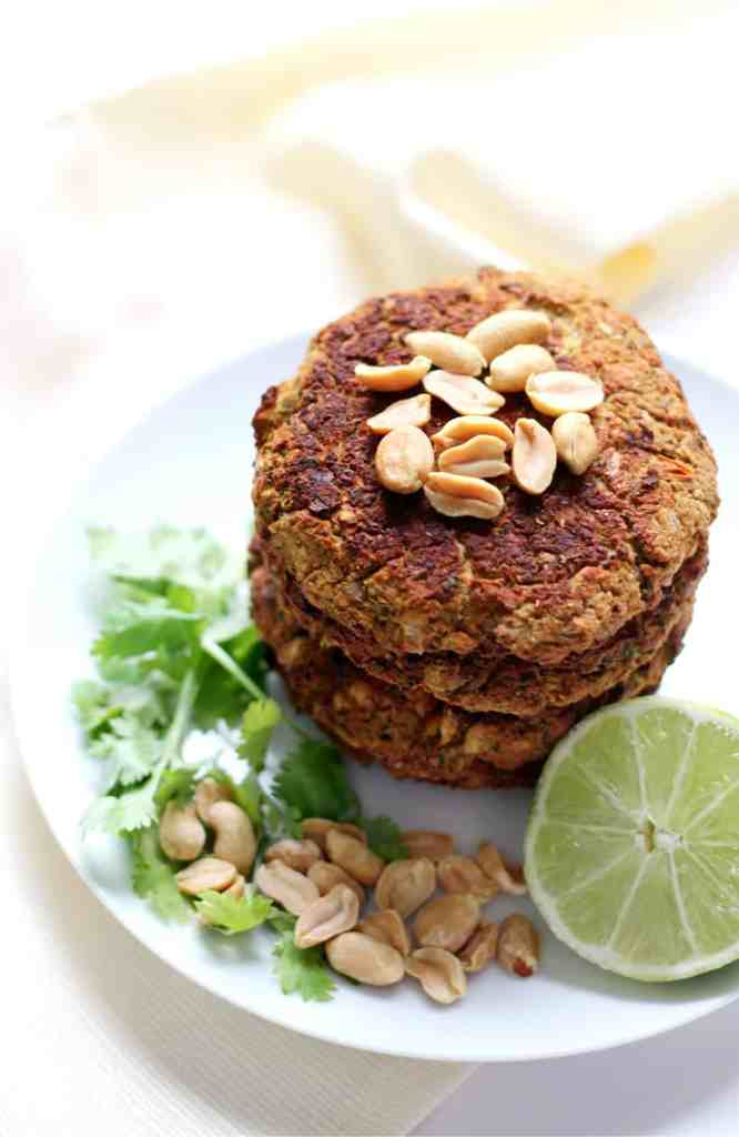 Three plain burger patties topped with nuts and a lime garnish.