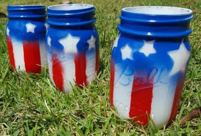 A mason jar spray painted to look like an American flag.