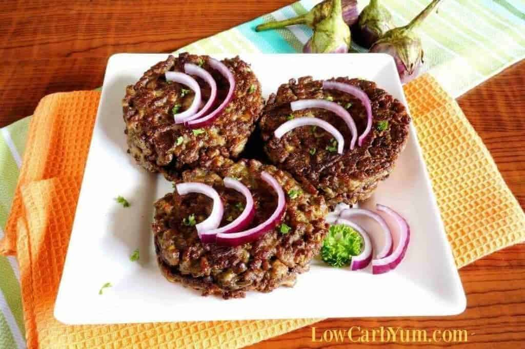 Eggplant burger patties with onions on a plate.
