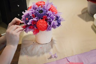 "Purple and pink cupcake ""flowers"" being added to a bouquet."
