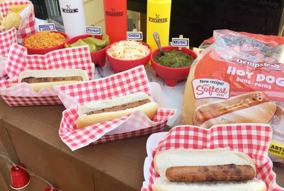 Hot dogs in baskets on a picnic table with condiments.