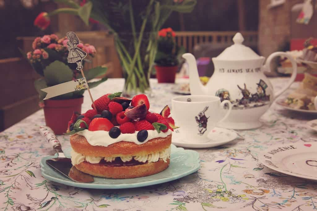 A mad hatter table setting complete with cake and teapot.