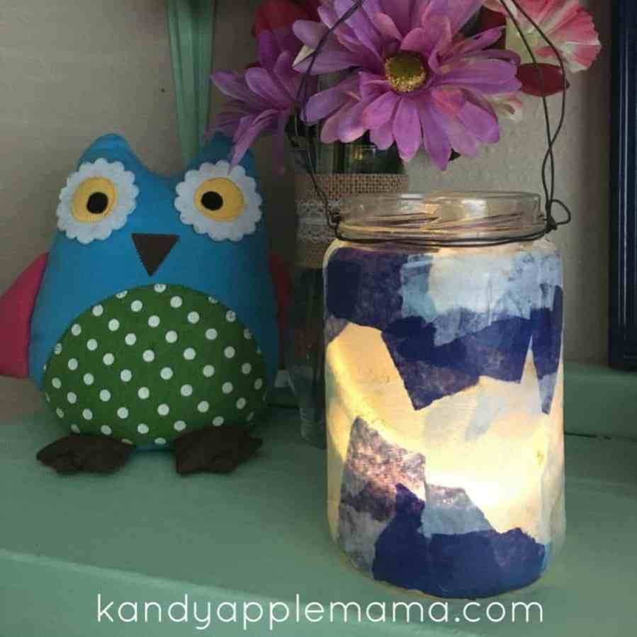 A mason jar light covered in colorful tissue paper.