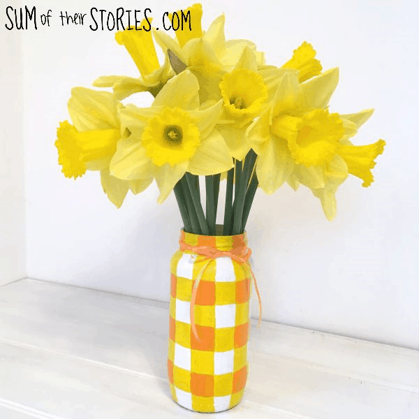 A yellow checkered mason jar vase.
