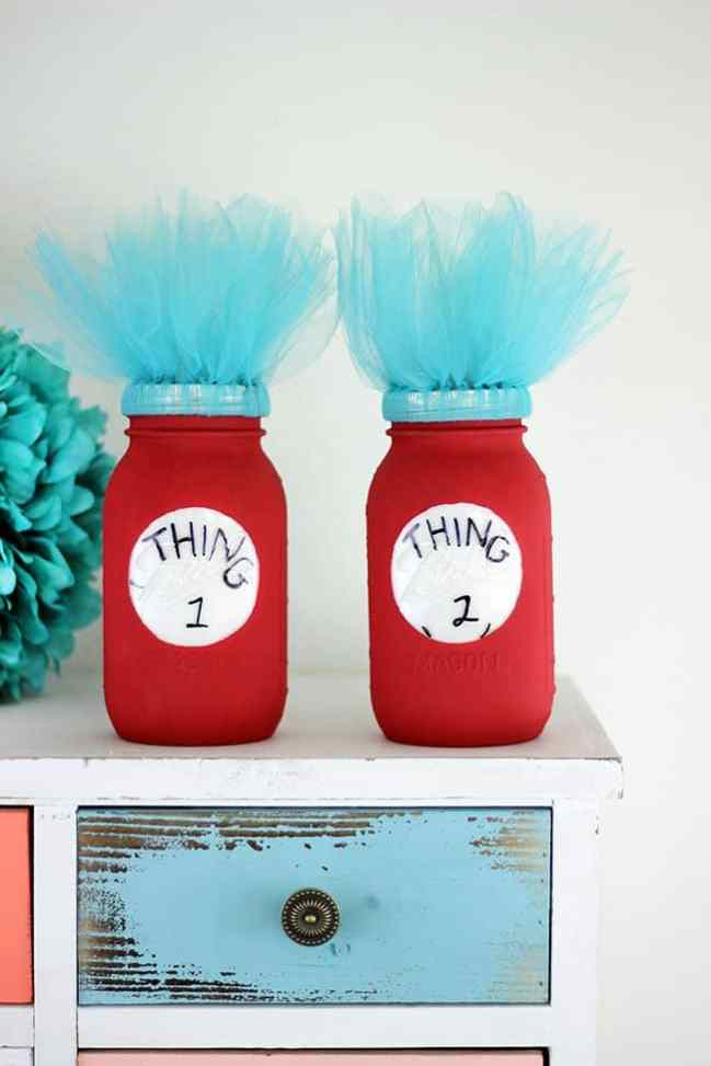 Two mason jars painted to look like Thing One and Thing Two from Dr. Suess.