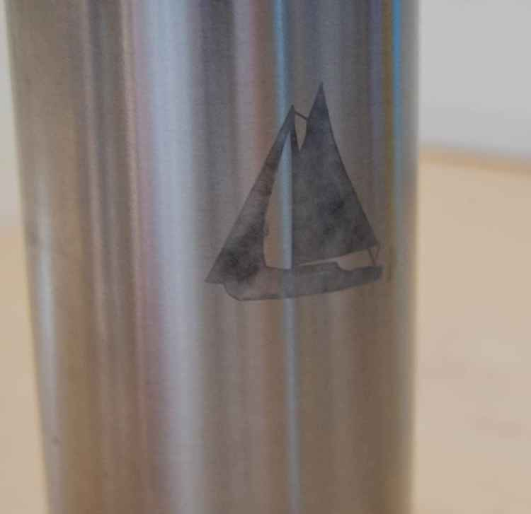 A metal water bottle with a boat etched into it