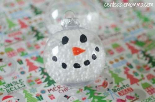 A DIY glass ball ornament filled with styromfoam balls and a snowman face drawn on.