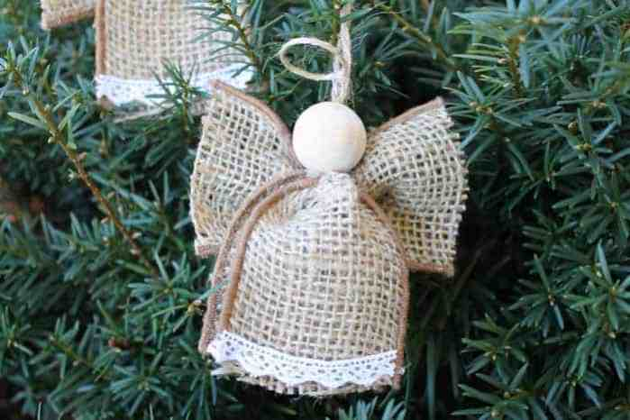 A burlap angel ornament with a wooden head and a touch of white lace/