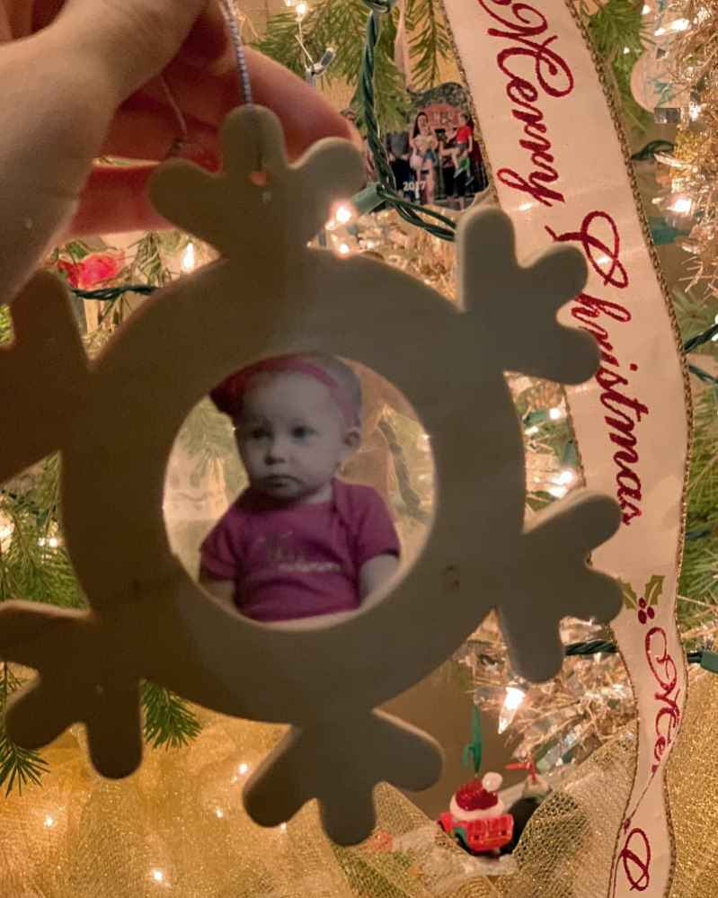 A Christmas ornament photo frame assembled but not painted with Christmas lights in the background.