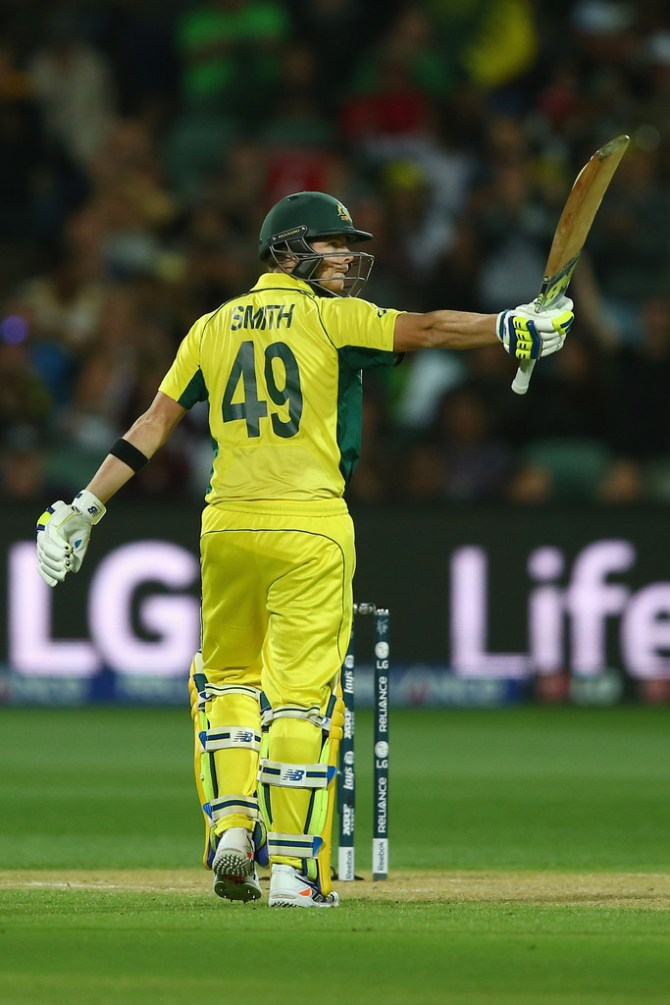 Smith raises his bat after scoring his half-century