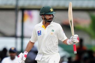 Shehzad raises his bat after bringing up his half-century