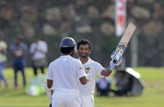 Karunaratne raises his bat after scoring his third Test century
