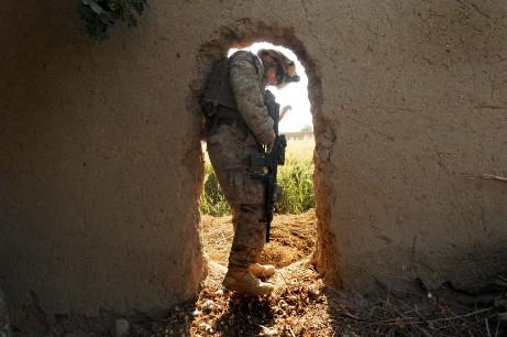 Sgt. Daniel Leith, of 3rd Battalion, 6th Marines, makes his way through a small doorway while searching the rear area of an abandoned compound while on patrol in Marjah, Afghanistan. The compound search began after AK47 shell casings were found in front of the structure during the patrol. Thomas Brown/Staff
