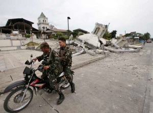 Filipino soldiers drive past a church, which was damaged in Tuesday's earthquake. The troops have requested water purification units from the Marine Corps as they help with disaster relief. (AP Photo/Bullit Marquez)
