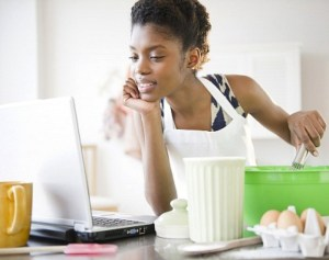 Woman cooking in kitchen with laptop