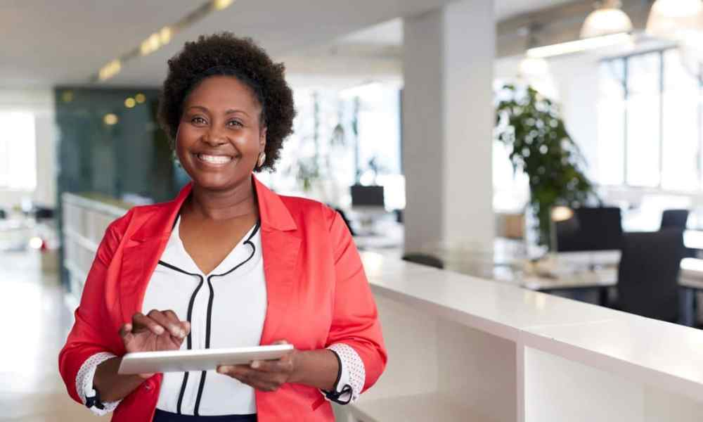 Black woman with short hair holding ipad in workplace
