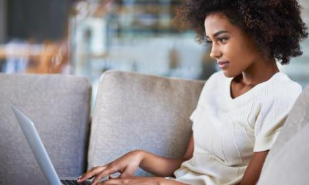 Young black woman typing on laptop g suite