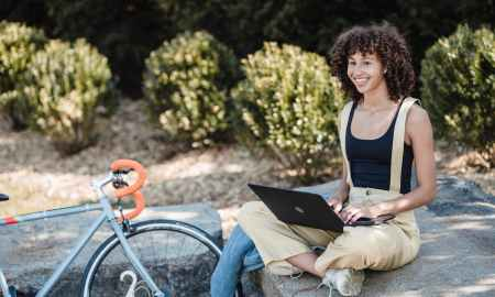 Black woman outdoors on laptop