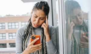 Black woman looking at phone