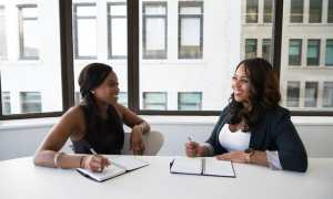 Two black businesswomen talking in an office