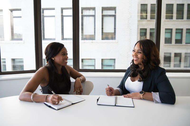 Two black businesswomen talking in an office