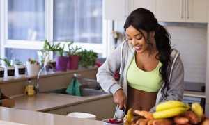 fit black woman slicing fruits