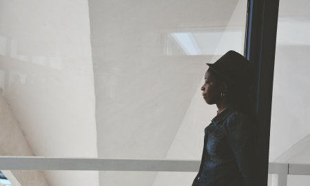 african american woman leaning against glass and thinking