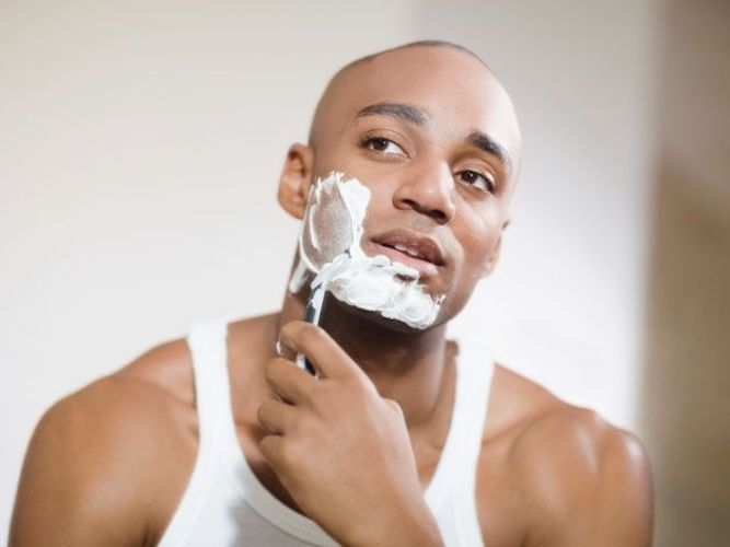 Young handsome man shaving his beard Premium Photo