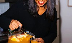 black woman smiling while pouring a glass of lemonade