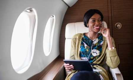 black woman sitting in private jet holding a tablet