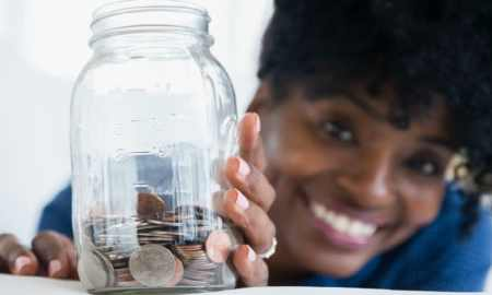 Black woman saving coins in jar