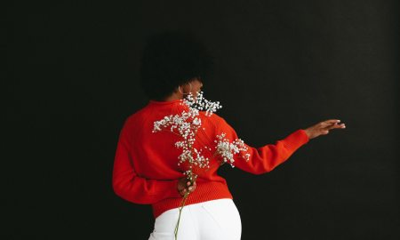 a black woman dancing and holding flowers