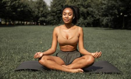 black woman meditating on grass
