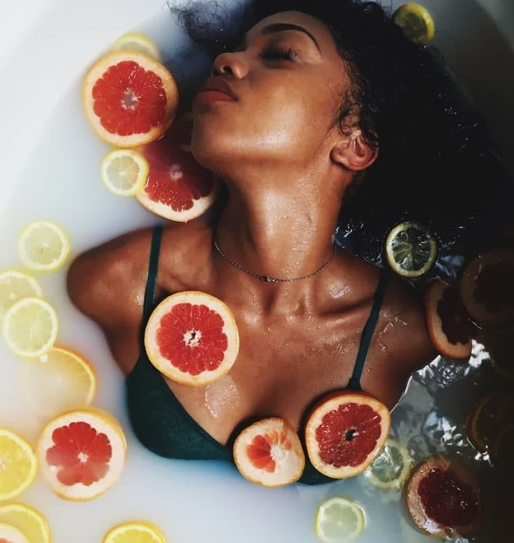 black woman in bathtub with flowers balance hormones