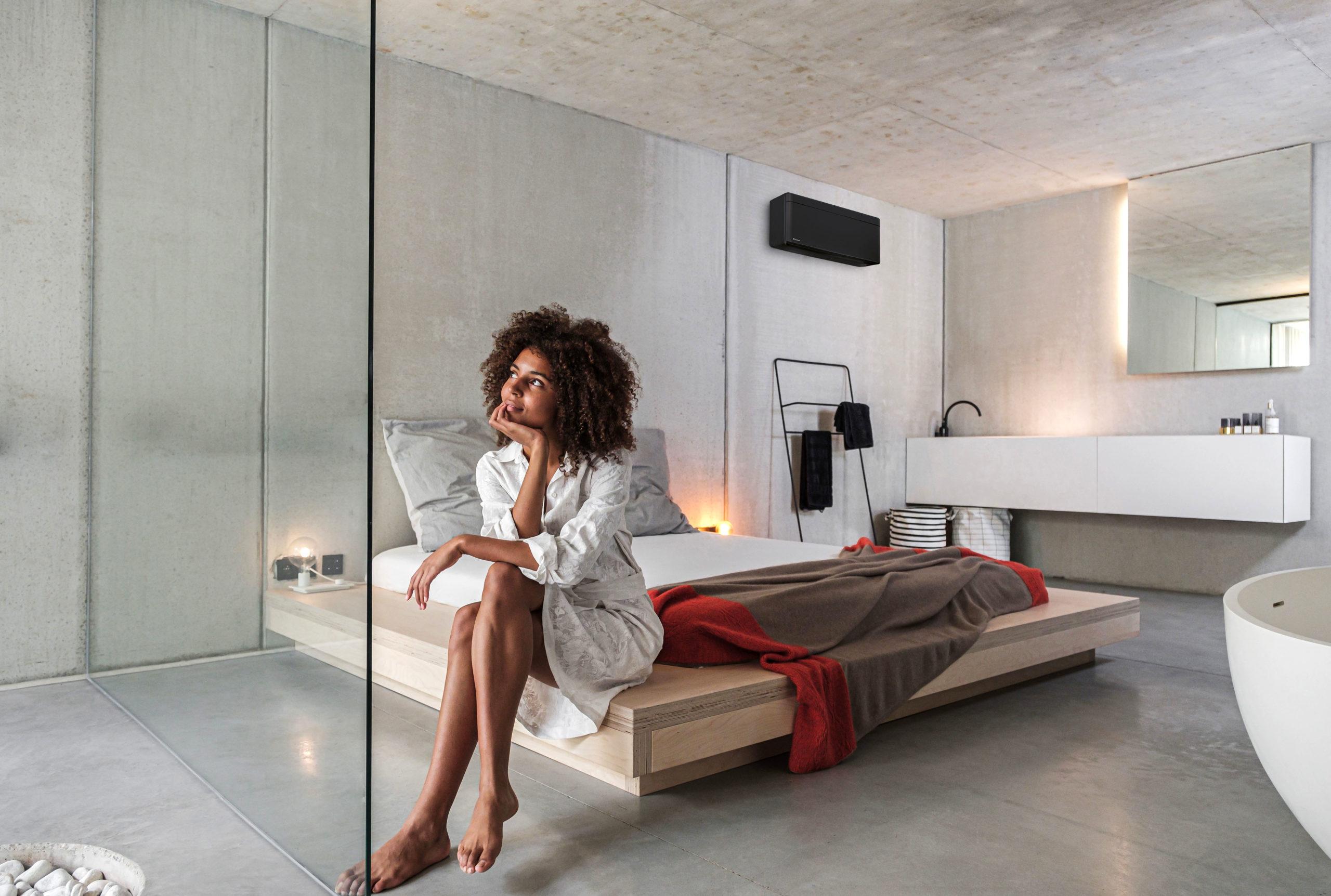 Frau geniesst die Klimaanlage im Schlafzimmer