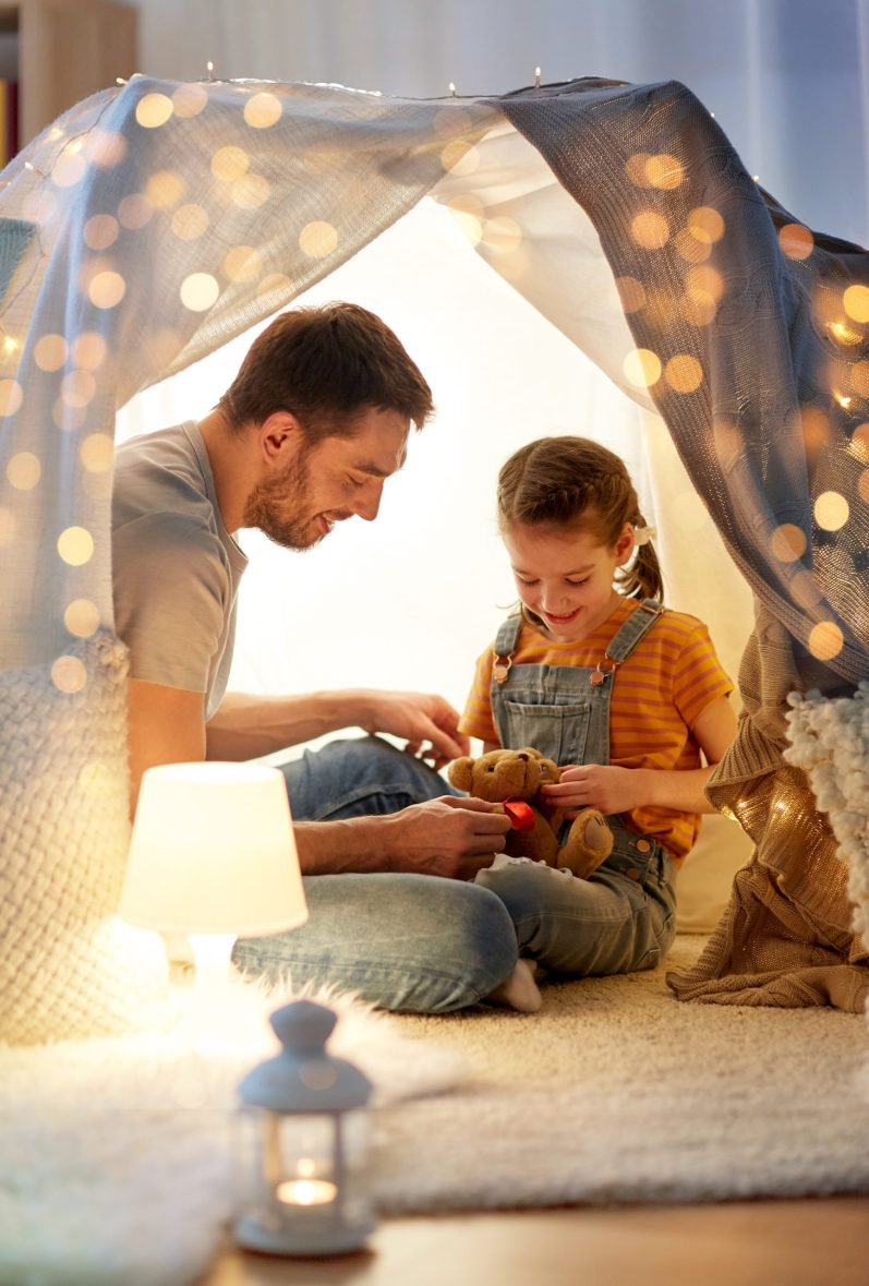 happy family playing with toy in kids tent at home