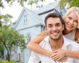 Ein junges Paar vor einem Einfamilienhaus