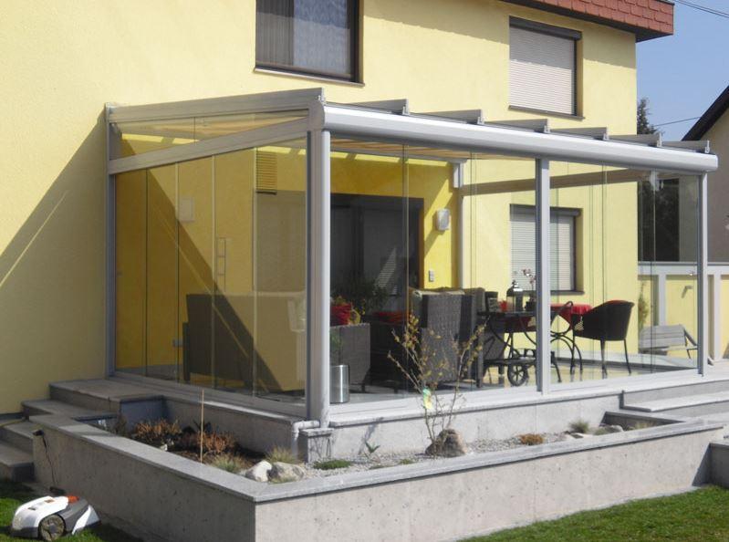 Terrassenverglasung vor gelbem Haus