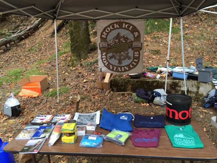 A Rock Ice & Mountain Club display table, featuring a variety of items including t-shirts and books