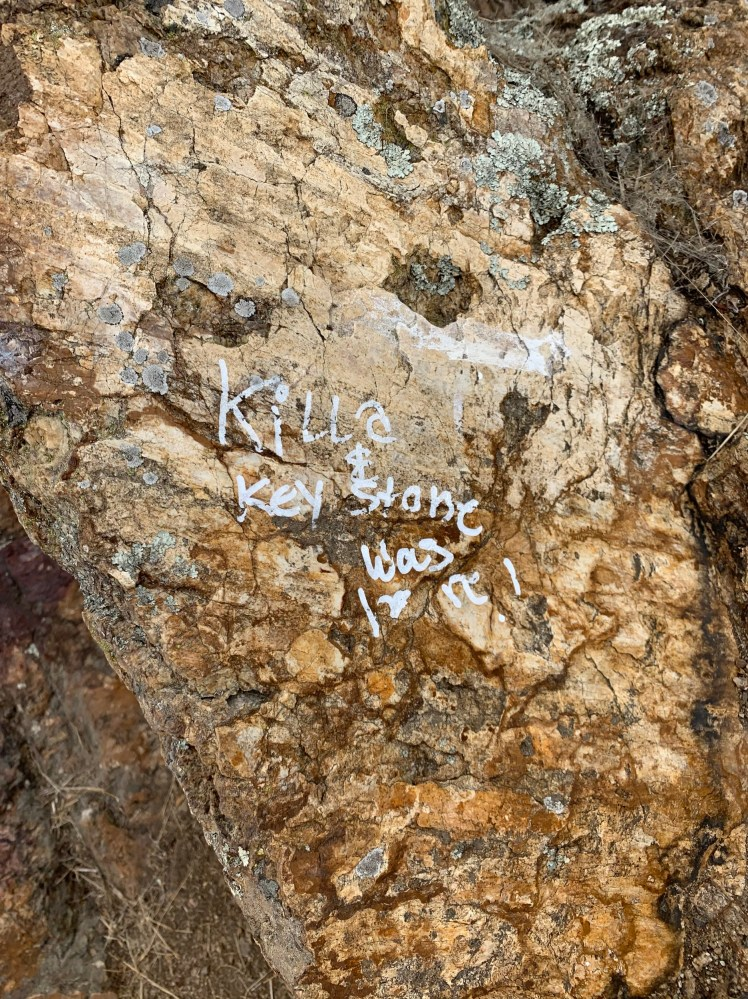 "graffiti reading ""killa & keystone was here!"" painted on a rock face"