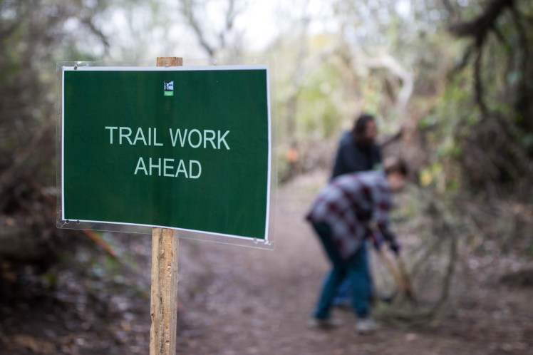 """A green sign reading """"Trail Work Ahead"""". In the background, out of focus, volunteers work on brush removal."""