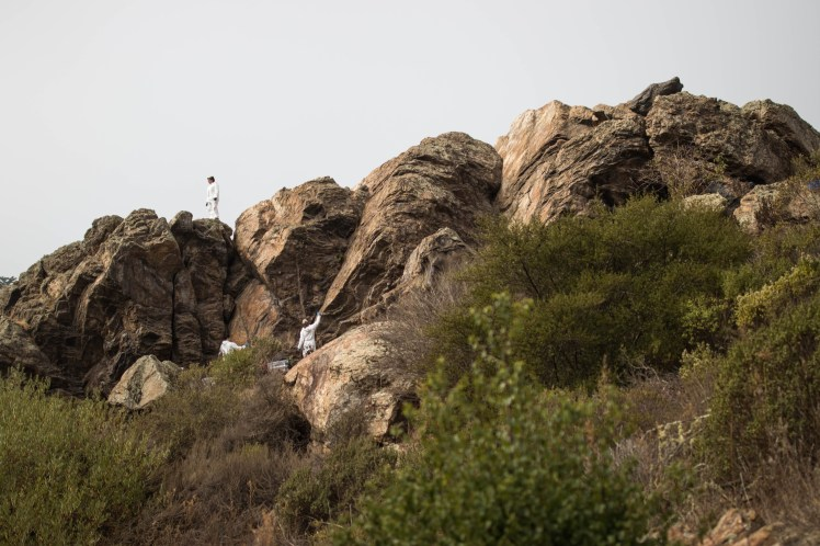 The boulders at Glen Canyon from a distance. A volunteer crew wearing Tyvek suits is removing graffiti. One crew member stands atop the boulders surveying the land.