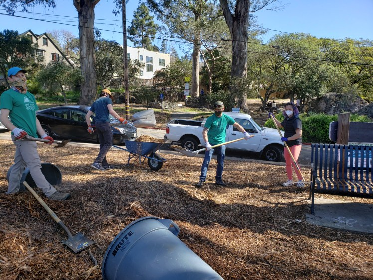 Masked volunteers shovel mulch from a pile into a wheelbarrow